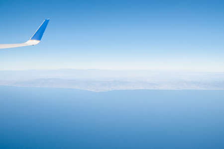 Hazy view of Californian coast from plane leaving Los Angeles. The blue sky and sea are split by the typical view of the coast largely obscured on the horizon on a beatuful clear day. Stock Photo