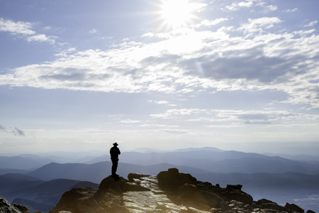 Sun filtered by clouds hits the rocky top on Mount Washington and the silhouette of man on top, New Hampshire, USA Stok Fotoğraf