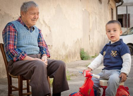 intergenerational: Italian grandfather sitting on old wooden chair in lane between homes caring for grandson looking towards camera on a red toy motorscooter.