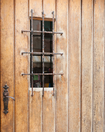 barred: Closed weatherd rustic door with barred window
