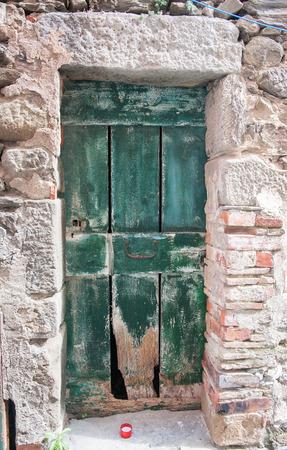 green door: Old green door in stone wall in Italian town in Cinque Terre area.