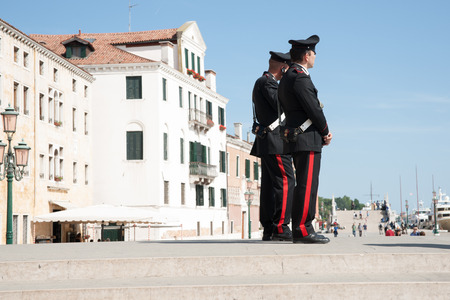 public safety: Venice, Italy - May 11, 2011 - Two Carabinieri stand watching events and keeping law on steps near Venice waterfront. Editorial