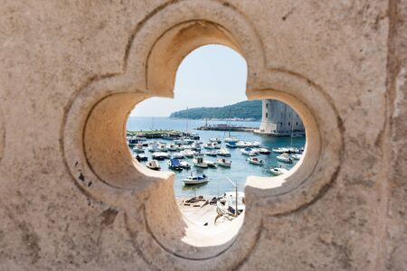 feature wall: Dubrovnik harbor through feature opening in ancient wall.