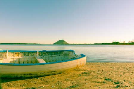 clinker: Vecchio sbiadito immagine effetto clinker dinghy cattura sole del mattino sulla spiaggia con il Monte Maunganui all'orizzonte. Archivio Fotografico