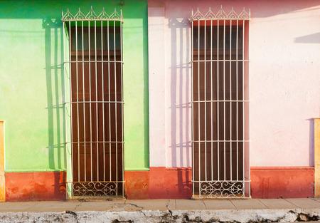 third world: Barred doors and broken pavement in third world town.