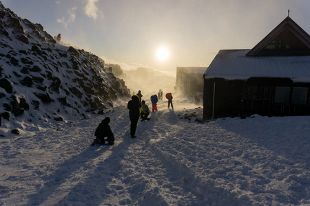 gusty: Unrecognisable people protect themselves and play backlit by fading sun in snow storm