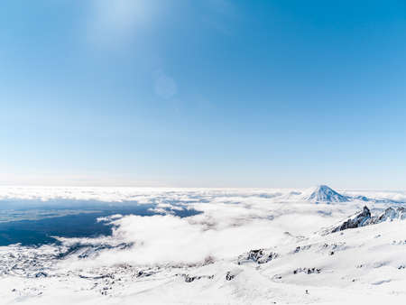 poking: Mount Ngauruhoe poking through clouds from slopes of Mt Ruapehu and Tongariro in distance. Stock Photo