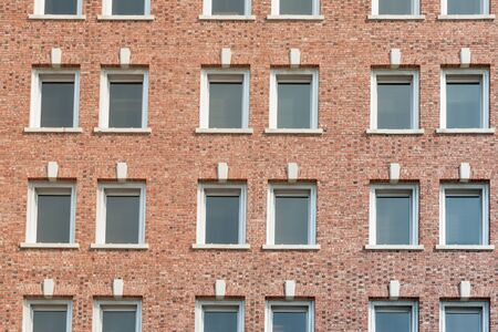 formality: Red brick wall with rows of windows building exterior full frame.