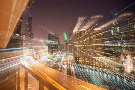urban architecture: Zoom light streams from city buildings at night accentuate the the density and skyline of architecture and cityscapes of  Chicago, Illinois, USA.