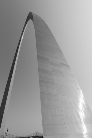st louis: St Louis Gateway Arch catches sun glistening as it towers into clear  sky with Martin Luther truss Bridge bottom of image. Abstract masterpiece of St Louis architecture, and famous arch, Missouri,USA.