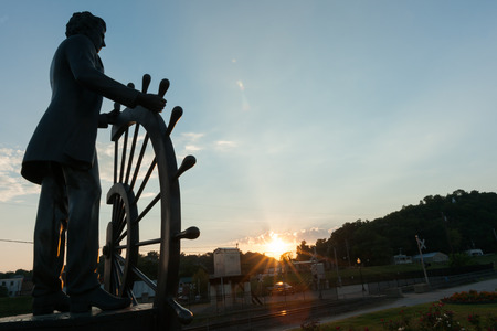 Bronze public art statue in Glascocks Landing looking over Mississippi River commemorates Mark Twains training as steamboat pilot silhouette in setting sun Hannibal Missouri USA historic hometown of Mark Twain. 版權商用圖片