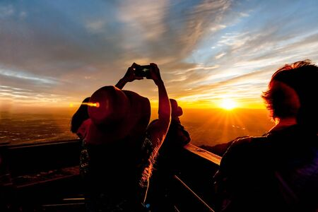 unrecognisable people: Silhouetted Tourists watch and photograph brilliant New Mexico sunset from Sandia Peak, Albuquerque, New Mexico, USA.
