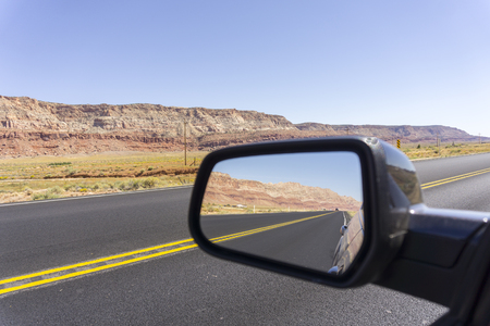 Road and landscape in rear vision mirror through  Arizona. Imagens