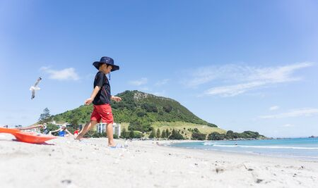 Mount maunganui, New Zealand - December 21, 2015; Boy in sun hat walks down Mount Maunganui beach towards waters edge on warm summer day. Editorial