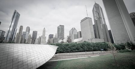 emphasised: Skating Ribbon through Chicagos Millennium Park projects into frame below the citys highrise cityscape forms a towering background on an overcast grey day emphasised by desaturated image. Stock Photo