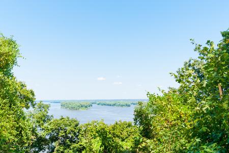 twain: Scenic green bushy edges of Mississippi River under clear blue sky near Hannibal Missouri USA historic hometown of Mark Twain