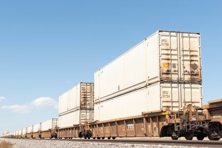 goods train: New mexico, September 20, 2015; Train laden with containers of goods  rolls though New Mexico high plains landscapes and railway alongside Route 66 focus point on midway containers. Editorial