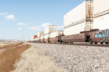 laden: New mexico, September 20, 2015;Train laden with containers of goods  rolls though New Mexico high plains landscapes and railway alongside Route 66 focus point on midway containers. Editorial