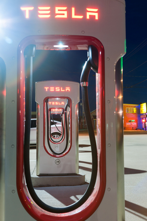 recharge: Shamrock, Texas, - September 11, 2015; Night image of Tesla battery recharge station looking through the cutaways to a series of the plugin rechargers with vehicle at end of the row in Shamrock Texas USA Editorial