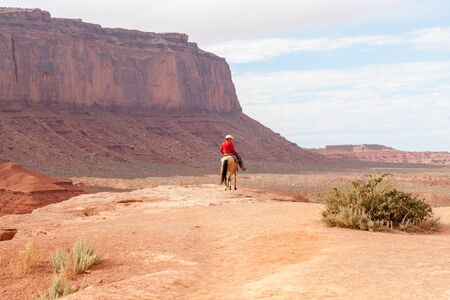 bluff: Monument Valley, USA - September 23, 2015; Cowboy caught in sun on rock bluff  while shadows settle on surround rock walls in Monument Valley Utah USA