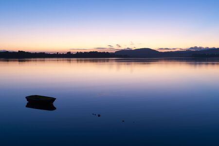 afloat: Silhouette of small boat afloat and distant hills across calm bay during brilliant sunrise.