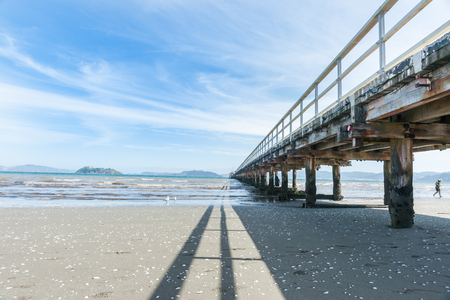 Long shadow Petone wharf and beach Wellington New Zealand