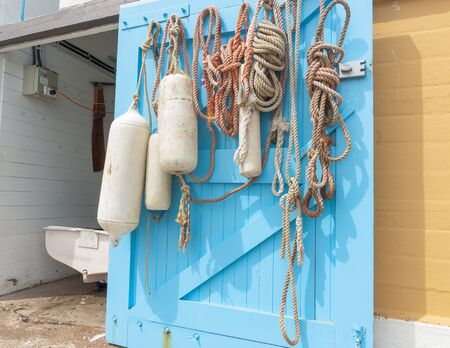 stern: Hanks of rope and buoys hanging on inside open blue boat shed door with dinghy stern in opening Stock Photo