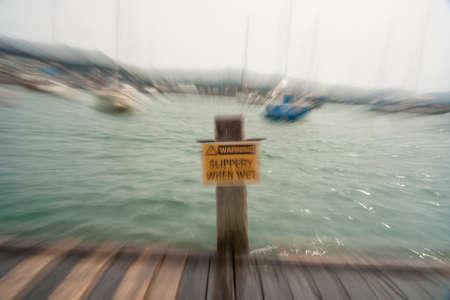when: Warning og danger near harbor Slippery when wet sign in zoom blur effect Stock Photo
