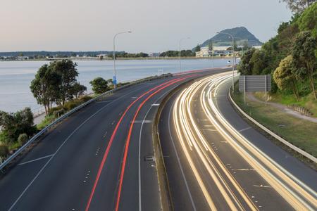 Highway lightstreams along Takitimu Drive at dusk looking north with Mount Maunganui on horizon. 版權商用圖片 - 56755979