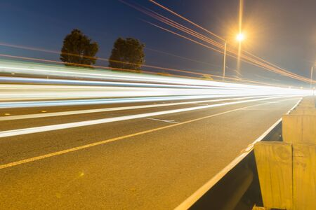 light streaks: Focus on car light streaks travelling along Tauranga Takitimu Expressway in dark of night with lights of vehicles streaming highlighting movement of cars passing along road dark sky and above