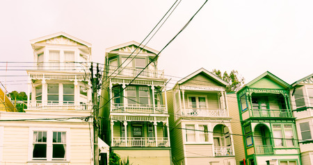 victorian architecture: Wellington suburban Victorian architecture old wooden multi-storied terrace homes with old power lines in reto style green hues Stock Photo