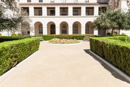 spanish style: Courtyard path lined with manicured hedge leads to round and garden seats in front of two level Spanish style portico Stock Photo