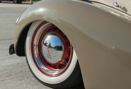hubcap: Pasadena, USA - October 4, 2015: American vintage car wheel close up with lens flare on shiny hubcap reflections of Packard and brand Chevrolet