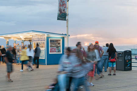 santa monica: SANTA MONICA, USA OCTOBER 5 2016: Santa Monica Pier long exposure tourists blurred moving about shopping the tourist kiosks on the pier at sunset in front of stalls October 5, 2015, Santa Monica, USA