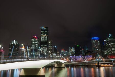 iluminated: Brisbane, Australia - April 27, 2016; Brisbane Victoria Bridge iluminated against dark and city building lights and colr reflections in calm water of Brisbane River