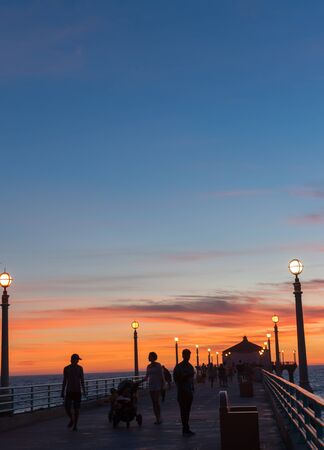 hued: People unrecognizable in silhouette on Manhattan Beach Pier Californian nights, at the pier at sunset as sun goes down and lights come on Editorial