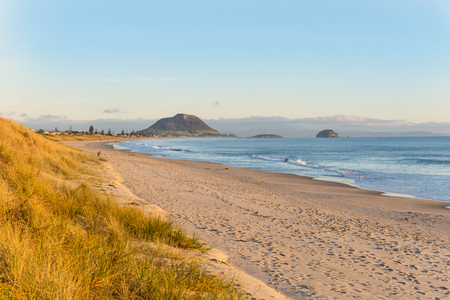 Papamoa at sunrise looking toward the Mount at end of beach Stock Photo