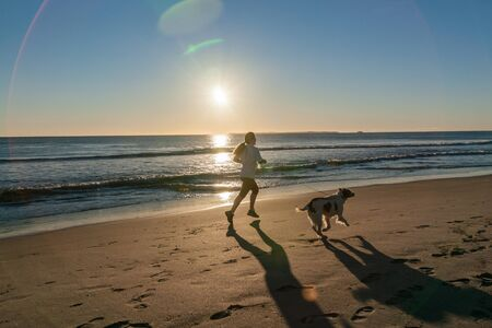 sillouette: Woman jogs blurred in motion along beach with dog sillouette on Papamoa Beach, outlok to horizon beautiful glow into into sunrise Stock Photo