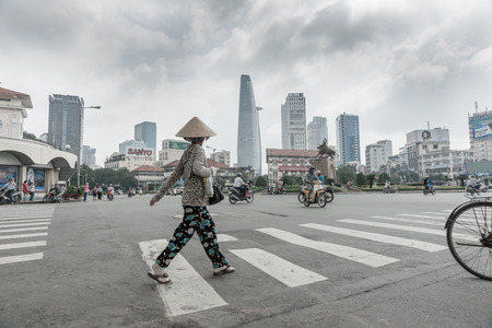 Vietnam, Saigon, Ho Chi Min City October 12, 2013;   overcast sky desaturated colors at major intersection in the city with woman crossing on pedestrian crossing wearing coolee hat while motor bikes and cycles seem to randomly move about Editorial