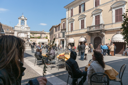 small town life: Looking into small Italian village square with people gathering in groups talking eating in modern life in historic Mediterranean town.