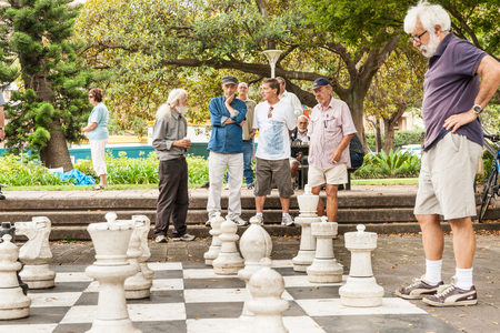 Sydney,Australia - January 29 2011; Group of men looking on in park in quiet contemplation while an outdoor game of chess is being played 版權商用圖片 - 59346006