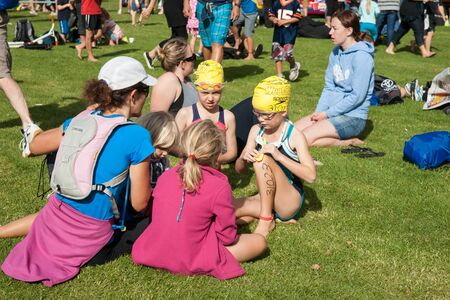 tog: Tauranga, New Zealand - April 1, 2012; Children on ground ready for swimming leg of event with swimming tog and caps with numbers waiting