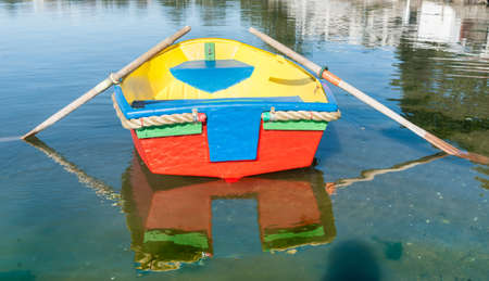 afloat: Brightly painted primary colors dinghy reflected in water