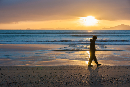 sunrises: Sunrises glistening across water onto beach as a lone boy walks silhouetted at waters edge and offshore islands seen from Waipu Cove New Zealand. Stock Photo