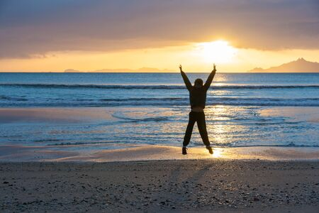waters edge: Sunrise glistens over water from horizon and off-shore islands as boy jumps with happiness on wintry morning at waters edge on beach Waipu Cove New Zealand Stock Photo