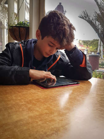 poised: Boy at table in low light in front of window resting  on his elbow concentrating with hand poised over his mobile device