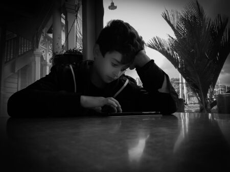 poised: Grainy effect black and white boy at table in low light in front of window resting  on his elbow concentrating with hand poised over his mobile device
