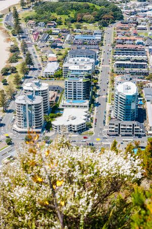 dominating: Mount Maunganui from mountain summit resort area with apartment buildings dominating the landscape close to base of mountain