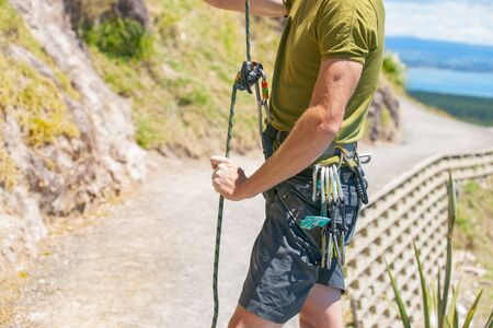 risk taking: Man readies for climb up a rock face with harness and rope and carabiners organised for the ascent Stock Photo