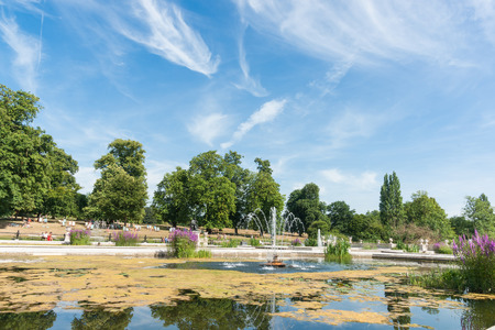 water feature: London, England - July 16, 2013; Wispy white clouds pattern blue sky over Kensington Garden London UK people out sunbathing deck chairs on the lawn and under large oak trees across park water feature. Editorial